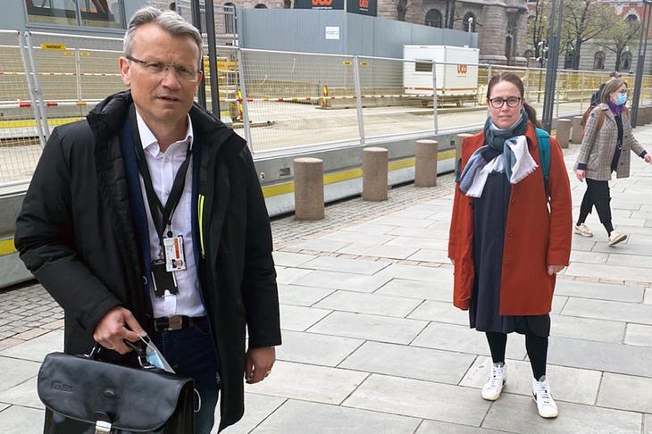 Egil André Aas står fremst i bildet med dokumentmappe og Kjersti Barsok står bak. Avsperret gate i bakgrunnen på grunn av bygningsarbeider. Tilfeldig forbipasserende ses i bakgrunnen.